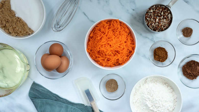 Carrots, eggs, flour, sugars, spices, oil in bowls on counter