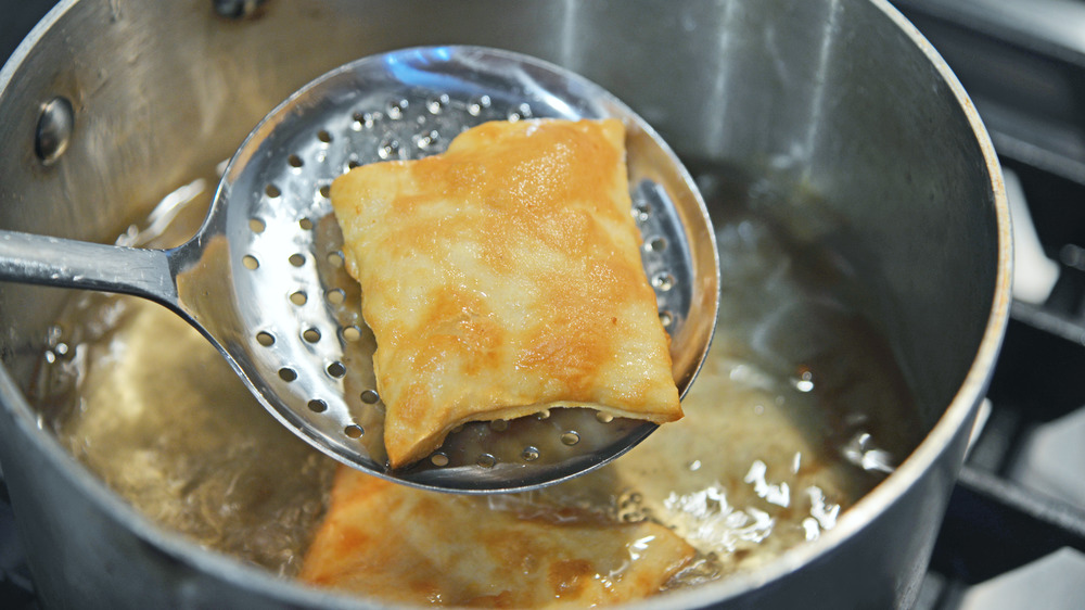 Removing fried sopapilla from oil