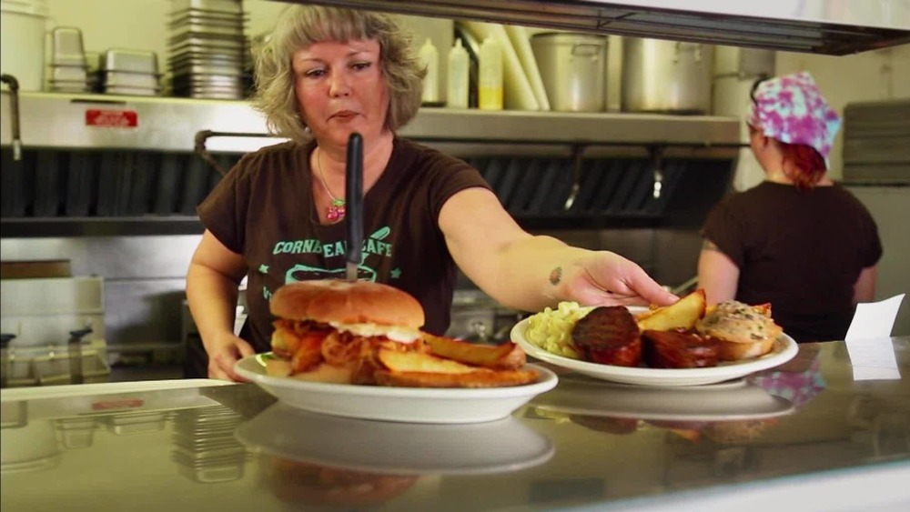 A woman in a restaurant kitchen serves up food